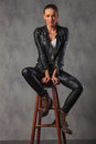 Attractive rocker woman in leather posing seated in studio Royalty Free Stock Photo
