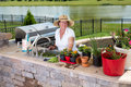 Attractive senior woman caring for her pot plants houseplants standing at the sink in outdoor summer kitchen with a watering can Royalty Free Stock Photo