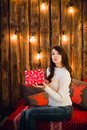 Attractive sensual young female with gift box sending a kiss over glittering background Royalty Free Stock Photo