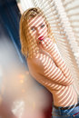 Attractive sexy beautiful young blond woman topless standing near window with flare sun lighting rayed through shutters portrait Stock Image