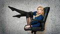 Attractive sexy blonde female with bright blue blouse and black stockings posing smiling sitting on office chair Stock Image