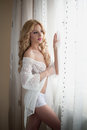Attractive sexy blonde with white lace lingerie near the curtains looking on the window. Portrait of sensual long fair hair woman Royalty Free Stock Photo