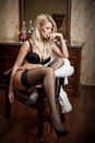 Attractive and sexy blonde woman with black bra and long stockings posing provocatively sitting on a chair. Beautiful woman Royalty Free Stock Photo