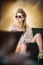 Attractive and sexy blonde woman with sunglasses posing provocatively sitting on chair, light brown background. Sensual female Royalty Free Stock Photo