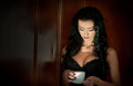 Attractive sexy brunette with black bra holding a white cup of coffee. Portrait of sensual woman in classic boudoir scene Royalty Free Stock Photo