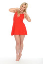 Attractive sexy cute young blonde woman wearing a short red mini dress haired in her twenties with bare feet with both hands under Stock Photography
