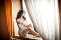 Attractive sexy girl in white dress posing provocatively in window frame. Portrait of sensual woman in classic boudoir scene Royalty Free Stock Photo