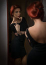 Attractive sexy redhead with black dress posing in front of large wall mirror. Portrait of sensual young woman with red hair Royalty Free Stock Photo