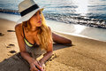 Attractive sexy woman in bikini and hat laying on sand on lonely beach sunrise sunset Royalty Free Stock Photos