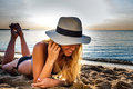 Attractive sexy woman in bikini and hat laying on sand on lonely beach sunrise sunset Royalty Free Stock Photo