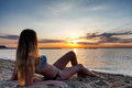 Attractive sexy woman in bikini laying on sand on lonely beach sunrise sunset Royalty Free Stock Images