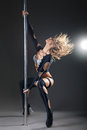 Attractive sexy woman pole dancer performing against grey background Stock Image