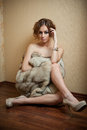 Attractive sexy young woman wrapped in a fur coat sitting on the floor in hotel room sensual redhead female being sad and Stock Photo