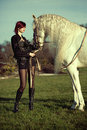 Attractive and shapely redhead with horse woman Stock Photo
