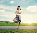 Attractive smiley woman in yoga pose standing on the road Stock Image