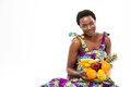 Attractive smiling african woman in colorful sundress holding exotic fruits Royalty Free Stock Photo