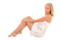 Attractive smiling blond in towel sitting over white background Royalty Free Stock Photography