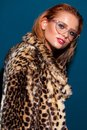 Attractive smiling girl with blue eyes, red hair, trendy glasses and in fur leopard coat. Studio portrait.