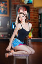 Attractive smiling pinup woman in denim shorts sitting on bar stool and drinking lemonade gorgeous model with white bow Stock Images