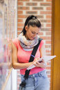 Attractive smiling student taking notes next to notice board Royalty Free Stock Photo