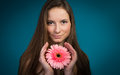 Attractive smiling woman portrait on blue background pretty girl with pink flower Royalty Free Stock Photography