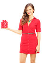 Attractive smiling woman in red dress holding a gift box isolated on white background Stock Images