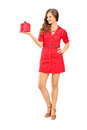 Attractive smiling woman in red dress holding a gift full length portrait of an isolated on white background Stock Photography