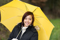 Attractive smiling woman under a yellow umbrella young asian sheltering as she takes walk outdoors on an inclement day Stock Photo