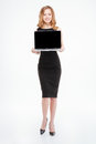 Attractive smiling young businesswoman standing and holding blank screen laptop Royalty Free Stock Photo