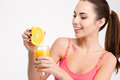 Attractive sportswoman in pink top squeezing orange making fresh juice Royalty Free Stock Photo