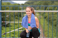 Attractive sporty girl holding bottled water as she crouches down on the side of a bridge over a railway line Stock Photography