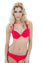 Attractive stern blonde model looking at camera in red bikini Royalty Free Stock Photo