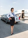 Attractive stewardess standing against limousine full length portrait of and private jet at airport terminal Stock Image