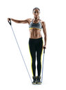 Attractive strong girl performs exercises using an resistance bands and looking at the camera Royalty Free Stock Photo