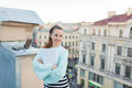 Attractive and stylish business woman holding a document and smiling while standing on the roof of the house in the Old town Royalty Free Stock Photo
