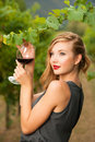 Attractive stylish woman drinking glass of red wine in vineyard Royalty Free Stock Photo