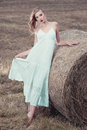 Attractive stylish Woman in  long white summe dress near hay bal Royalty Free Stock Photo