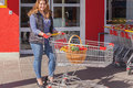 Attractive stylish woman shopping for groceries standing with a trolley and basket full of fresh fruit and vegetables at the Stock Photo