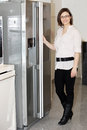 Attractive stylish young housewife in the kitchen standing at the door to the refrigerator Royalty Free Stock Photo