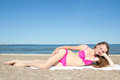 Attractive teenage girl lying at the beach in bikini Royalty Free Stock Images