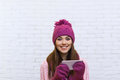 Attractive teenage girl texting message communication using cell smart phone over white brick background Royalty Free Stock Photo