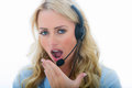 Attractive tired or bored young business woman using a telephone headset board yawning calling clients cold calling insurance Stock Image