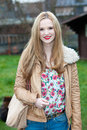 Attractive trendy young teenage girl with long straight blond hair standing in a garden wearing a stylish jacket with a bag over Stock Photos