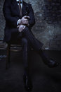 Attractive villain sitting with his legs crossed