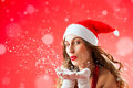 Attractive woman as Santa Claus blowing snow Stock Photography