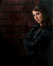 Attractive woman with attitude and brick wall model leather jacket long hair against a Royalty Free Stock Images