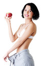 Attractive woman in baggy trousers with apple isolated on white Stock Photo