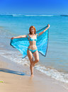 Attractive woman on a beach with a blue scarf in hands Royalty Free Stock Photo