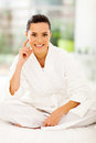 Attractive woman bed wearing white bathrobe sitting on Stock Photos