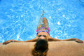 Attractive woman in bikini and sunglasses sunbathing leaning on edge of holidays resort swimming pool Royalty Free Stock Photo